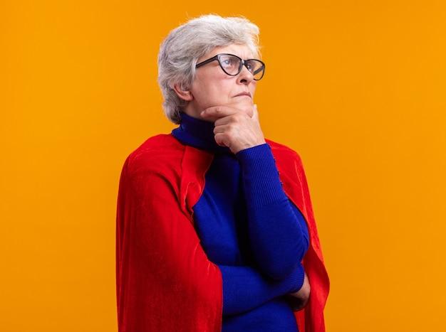 オレンジ色の背景の上に立って物思いにふける表現を考えて脇を見て赤いマントを着て眼鏡をかけた年配の女性のスーパーヒーロー