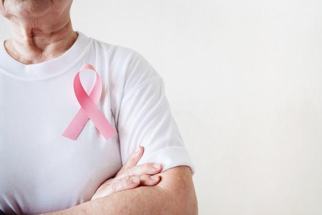 Пожилая женщина поддерживает день рака молочной железы, наклеив на грудь розовую ленточку «осведомленность о раке груди»