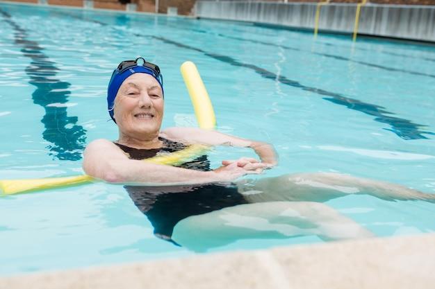 레저 센터에서 수영장에서 수영하는 고위 여자