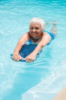 Старшая женщина плавает в бассейне в солнечный день