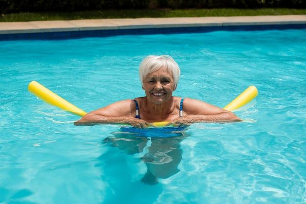 Старшая женщина плавание с надувной трубкой в бассейне