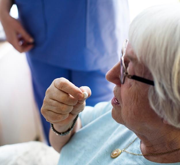 Старший женщина, принимая лекарство