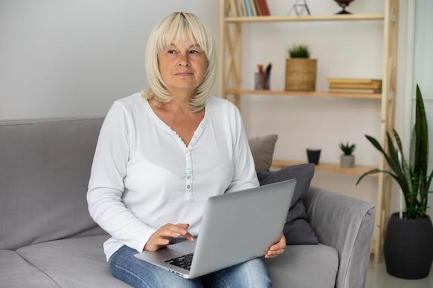 Старшая женщина, занимающаяся онлайн-классом на своем ноутбуке дома