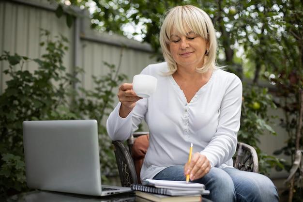 집에서 노트북으로 온라인 수업을 듣는 시니어 여성