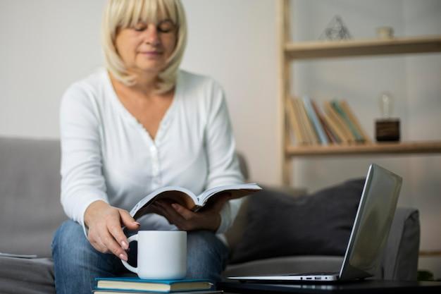 自宅でノートパソコンでオンラインクラスを受講している年配の女性