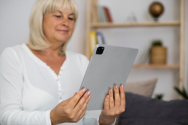 Старшая женщина принимает онлайн-класс на своем планшете