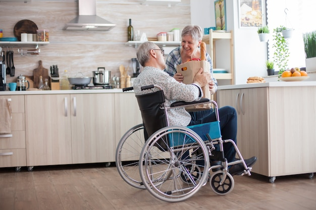 Senior woman taking grocery paper bag from handicapped husband in wheelchair. mature people with fresh vegetables from market. living with disabled person with walking disabilities