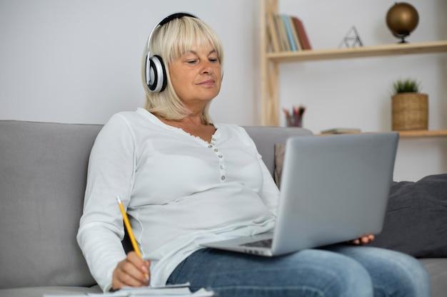 Donna anziana che segue una lezione online sul suo laptop a casa