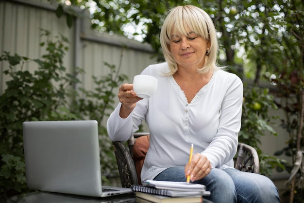 Senior woman taking an online class on her laptop at home