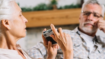 Senior woman taking photo of her husband from camera