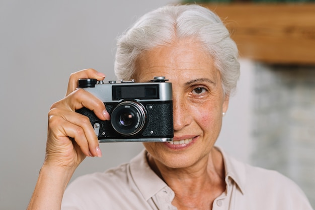Senior woman taking picture with camera