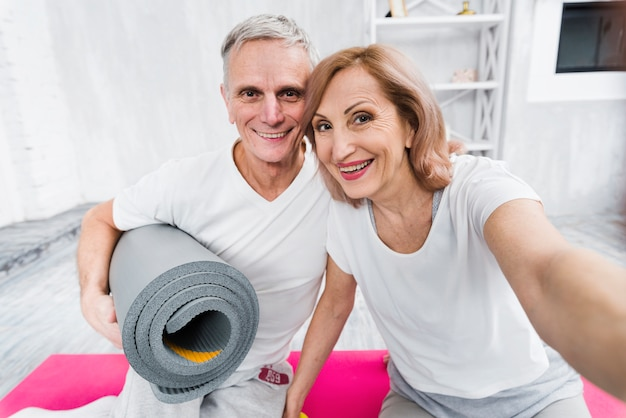 Senior woman taking selfie with her husband holding rolled yoga mat at home