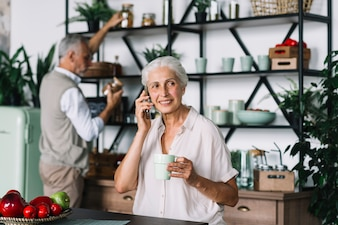 Senior woman talking on cell phone holding coffee cup sitting in front of man taking bottles from shelf