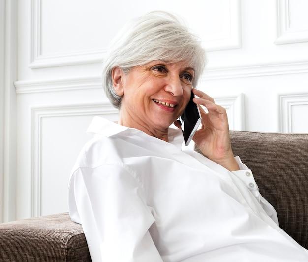 집에서 전화 통화를 하는 시니어 여성