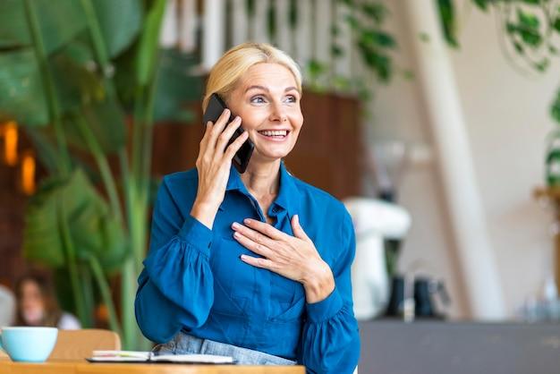 Старшая женщина разговаривает по телефону во время работы