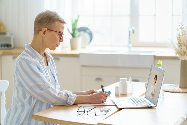 Senior woman talking online with doctor during covid  while sitting in kitchen at home
