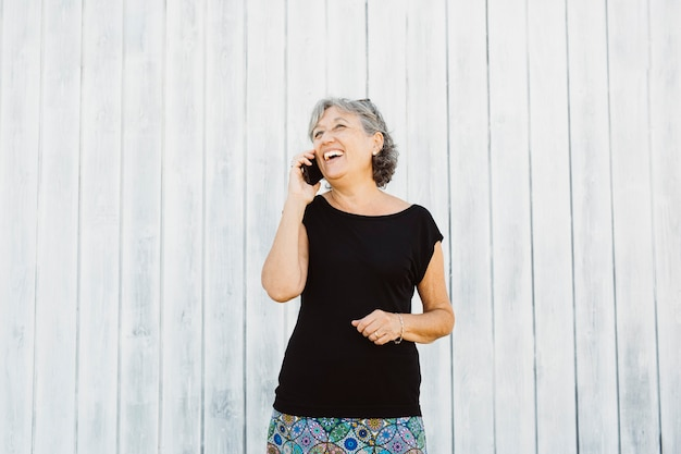Senior woman talking on a phone over a white wooden backgroound