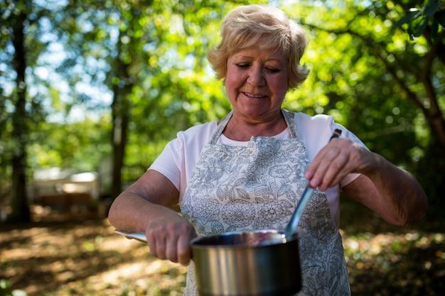 Senior woman tasting jam in garden