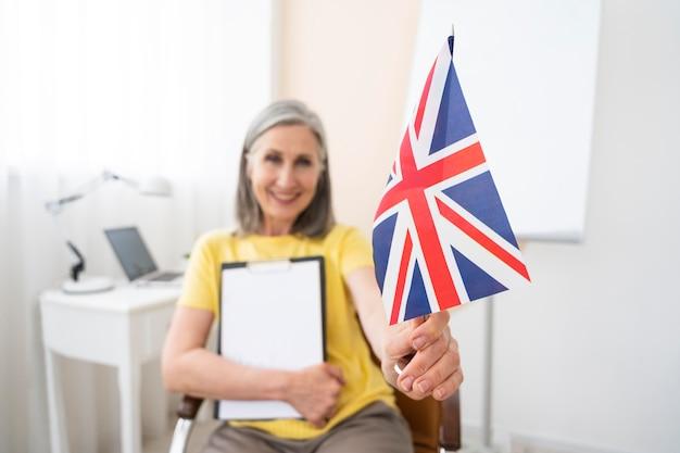 Старшая женщина преподает уроки английского онлайн дома