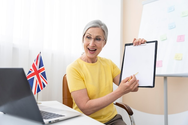 Старшая женщина преподает уроки английского языка