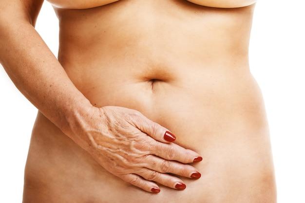 Senior woman touching abdomen over white background