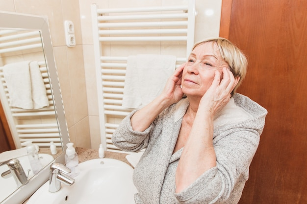 Senior woman touching her soft face skin and does massage