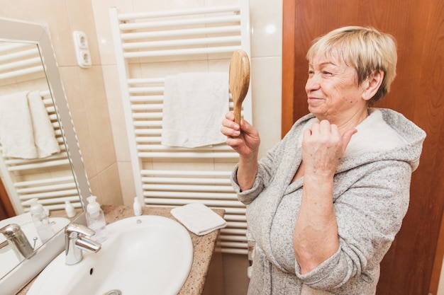 Senior woman touching her soft face skin and looking in hand mirror at home