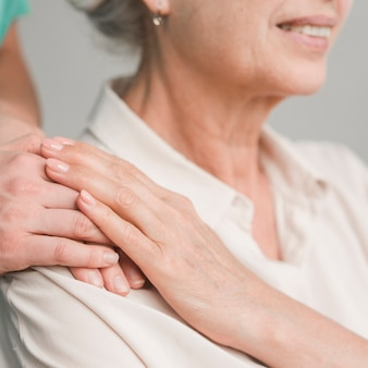 Senior woman touching nurse hand
