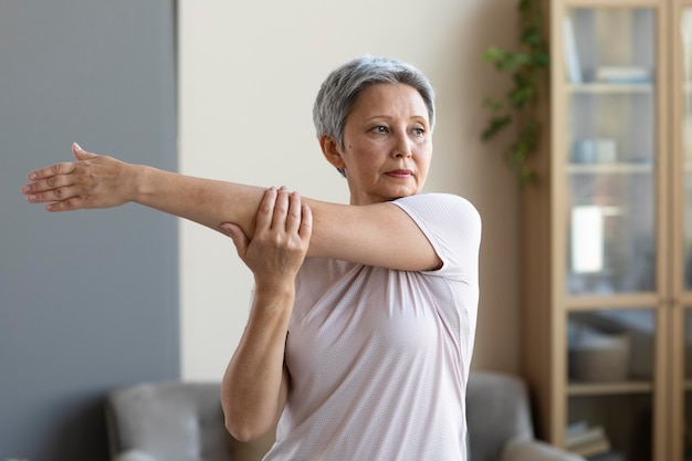 Старшая женщина тренируется дома