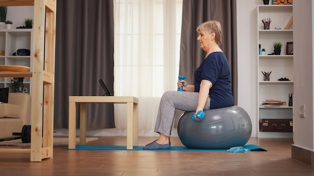 オンラインレッスンで安定ボールウォッチングで上腕二頭筋をトレーニングする年配の女性。オンライントレーニング学習技術老婆リフティングトレーニング健康的なライフスタイルスポーツフィットネストレーニング自宅でウエイトダム
