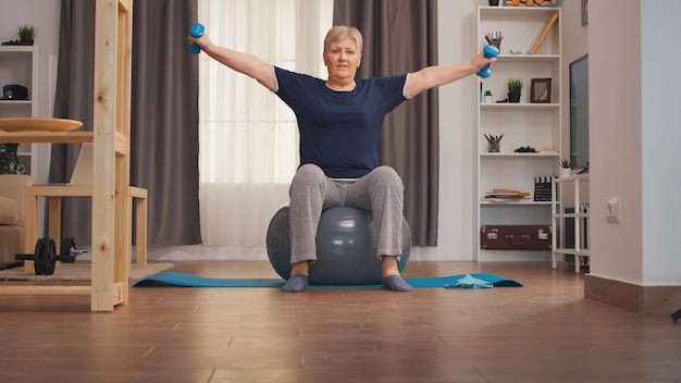 スイスのボールに座っているダンベルで肩を訓練する年配の女性。ウエイトダンベル活動で自宅でトレーニング健康的なライフスタイルスポーツフィットネストレーニングを持ち上げる老婆
