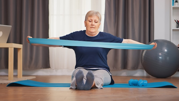 ヨガマットの上に座ってレジスタンスバンドでトレーニングする年配の女性。年金受給者の老婆は、退職時に健康的なライフスタイルを生きるフィットネスを伸ばし、自宅での運動を訓練します