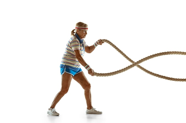 白い壁にスポーツウェアのロープでトレーニングする年配の女性