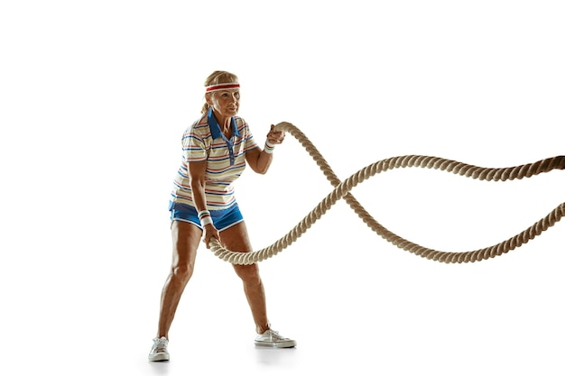 Senior woman training with ropes in sportwear on white background