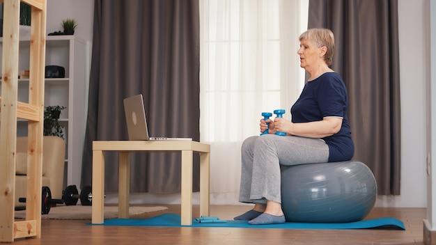 オンラインフィットネスレッスン中にスタビリティボールに座ってウェイトトレーニングをする年配の女性。オンライントレーニング学習技術老婆リフティングトレーニング健康的なライフスタイルスポーツフィットネストレーニングhomで