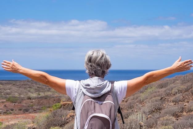 両手を広げて海の上の地平線を見ながら、アウトドアトレッキングを楽しんでいる年配の女性旅行者