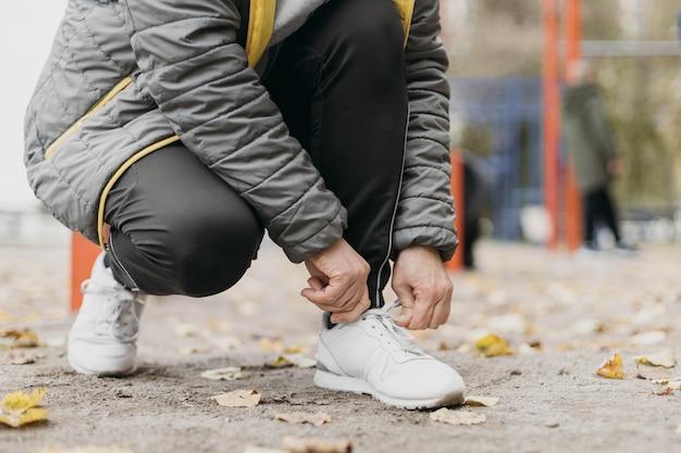 屋外で運動する前に靴ひもを結ぶ年配の女性