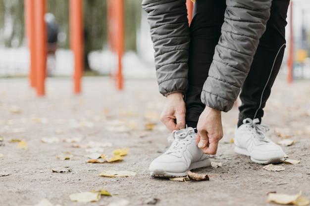 コピースペースで運動する前に彼女の靴ひもを結ぶ年配の女性