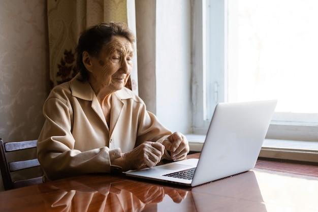 Старший компьтер-книжка пользы женщины. она выглядит очень удивленной. серфинг в браузере и социальных сетях. ноутбук на столе. использование технологий в концепции старости