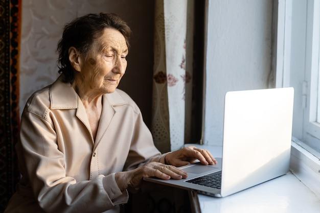 고위 여자는 노트북을 사용합니다. 그녀는 매우 놀란 것 같습니다. 브라우저 및 소셜 미디어에서 서핑. 테이블에 노트북입니다. 노년 개념에서 기술 사용