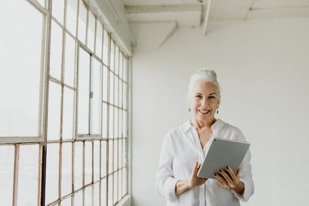 흰색 방에 있는 창가에서 디지털 태블릿을 사용하는 시니어 여성
