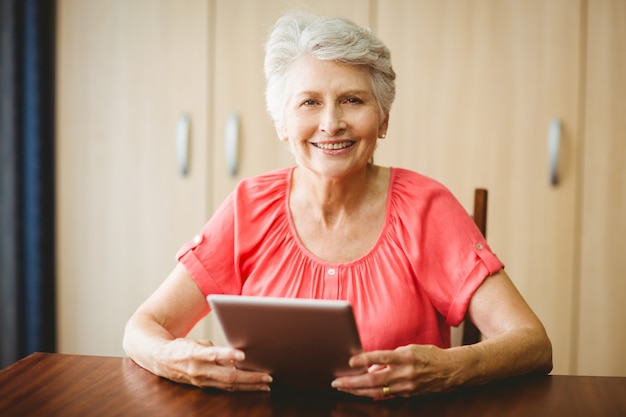 Старшая женщина используя таблетку