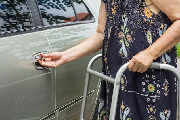 駐車場で歩行器を使用して年配の女性