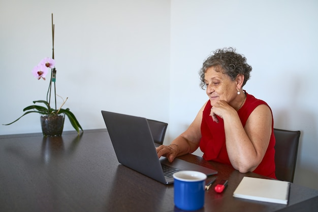 コンピューターを使用して自宅からインターネットを閲覧する年配の女性
