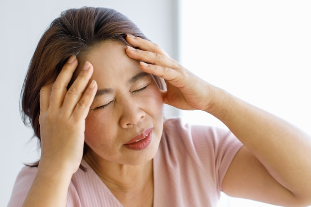 脳血管障害や脳卒中などの頭痛で、手を使って頭を痛めたり、顔を歪ませたりする年配の女性。