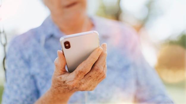 公園で携帯電話を使用している年配の女性