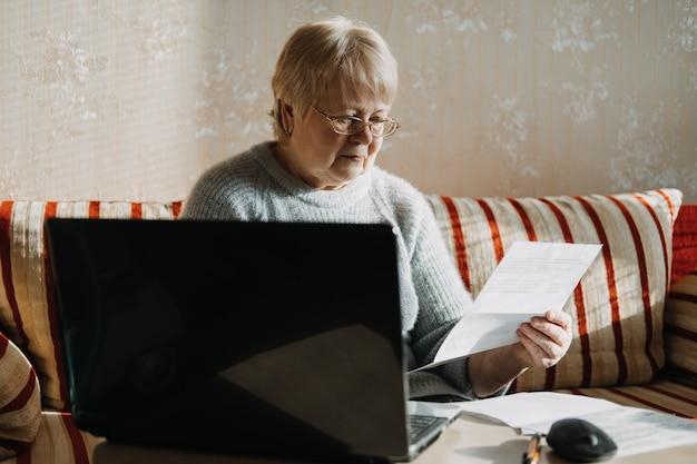 ノートパソコンを使用し、自宅で書類を持っている年配の女性。オンラインで金融銀行のローンや住宅ローンのドキュメントを操作するコンピューターを使用して、成熟した高齢の女性に焦点を当てました。
