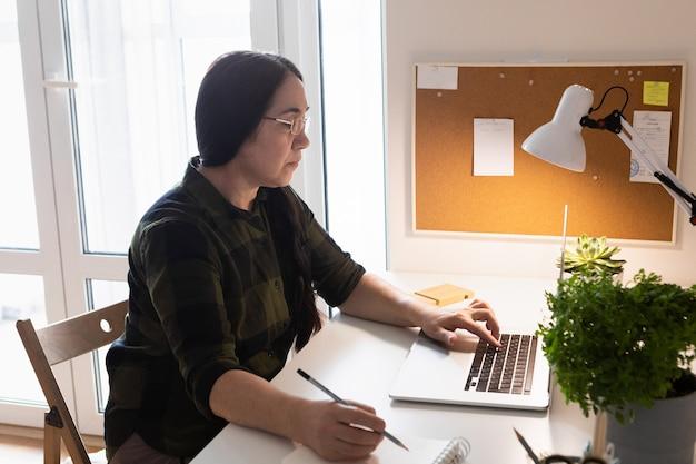 Старшая женщина, использующая ноутбук в домашнем офисе.