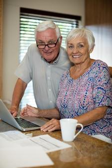 Старшая женщина, использующая ноутбук на кухне дома