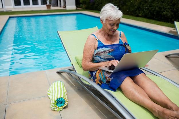 수영장에서 라운지의 자에 노트북을 사용 하여 고위 여자